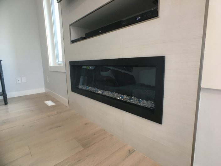 fireplace renovations with custom tile and electric fireplace