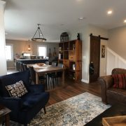 dining living room with laminate floor barn door and wainscot